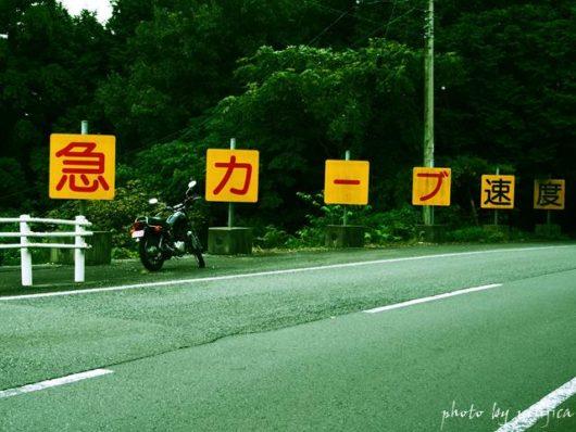急カーブ看板とバイクのある風景