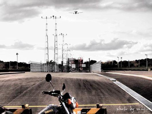 バイクと進入灯を通過する飛行機