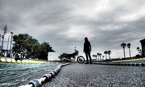 漁港の網干しとバイクのある風景