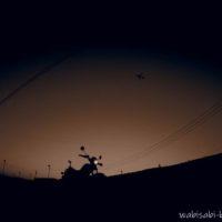 日暮れの茶畑とオートバイ