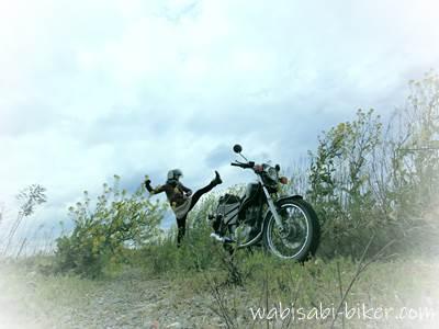 キックする女性バイク乗りと菜の花