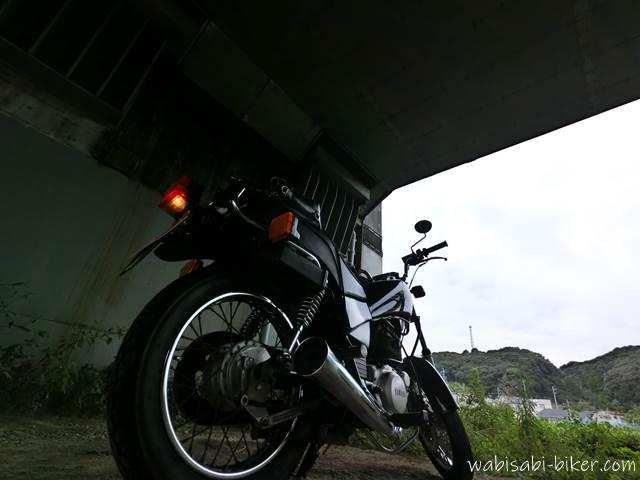 ガード下で雨宿りするオートバイ