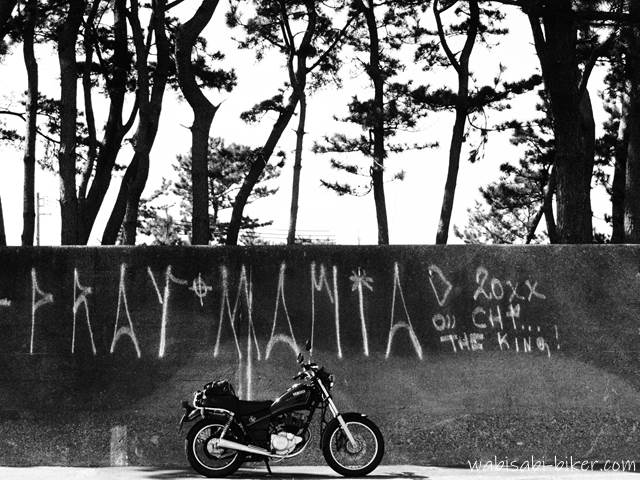 落書きされた防潮堤とオートバイ