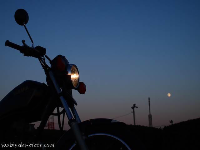 オートバイと十三夜月のある夕景