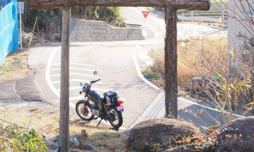 ツルの絡んだ木の鳥居とオートバイ