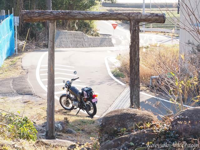 蔦の絡んだ木の鳥居とオートバイ