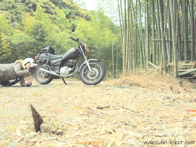 タケノコとオートバイとカメラを構える女性ライダー