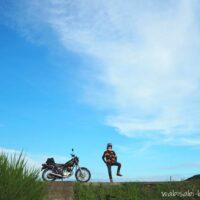 青空とオートバイとポーズを取るライダー